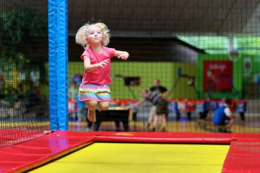 Little child jumping at trampoline
