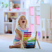 Happy toddler girl playing with abacus