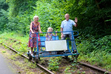 Grandparents with grandchild riding rail-bike