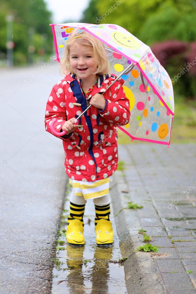 Happy little girl having fun under the rain