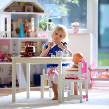 Little girl having playing tea party with dolls