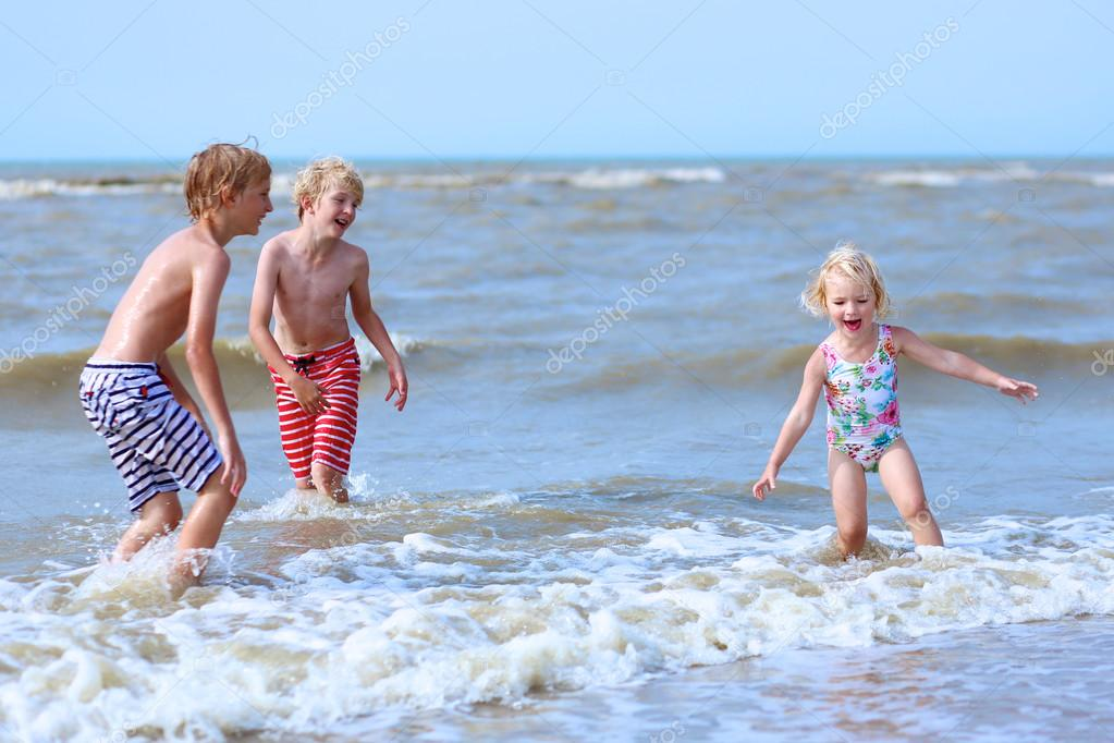 Happy children splashing in the sea