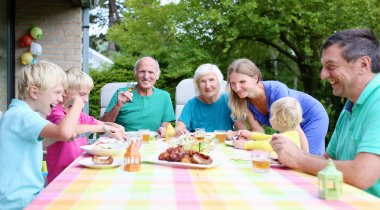 Big family of seven having meal outdoors