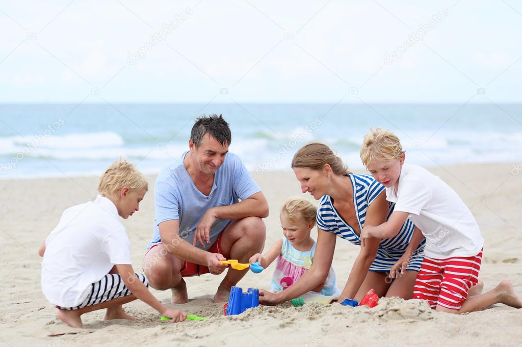 Happy family of five having fun on the beach