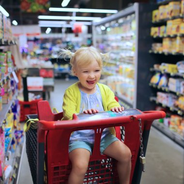 Funny little child sitting in the trolley in hypermarket