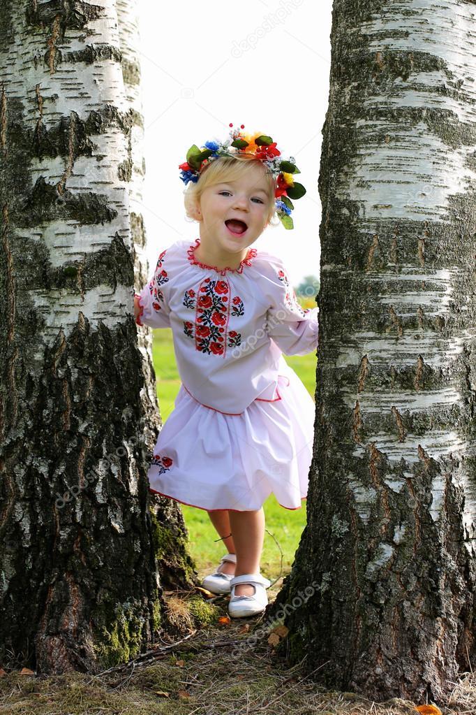 Little Ukrainian girl in traditional dress playing in the fields