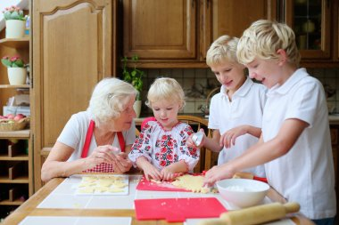 Grandmother with grandkids cooking in the kitchen