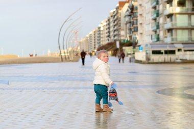 Lovely baby girl walking on beach promenade