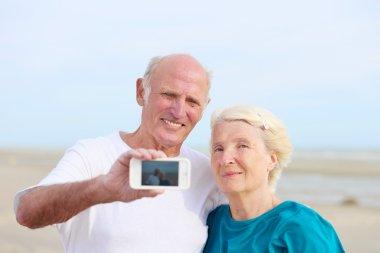 Senior couple taking self mobile photo on the beach