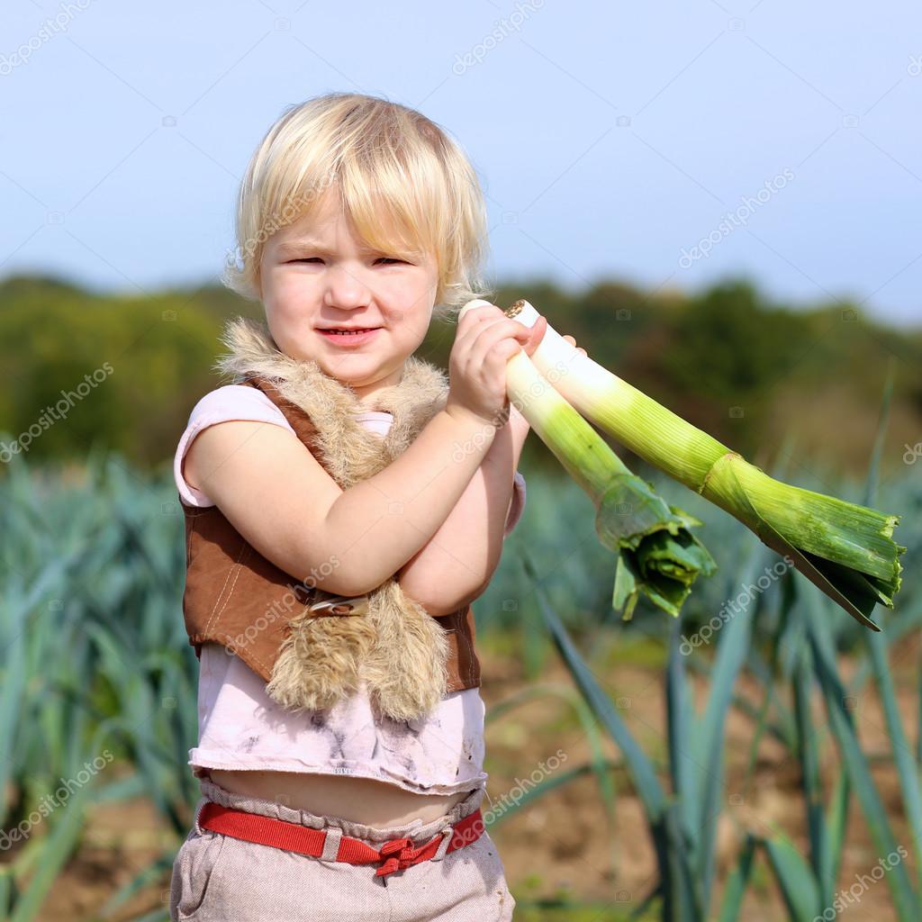 Adorable little girl harvesting leek in the field