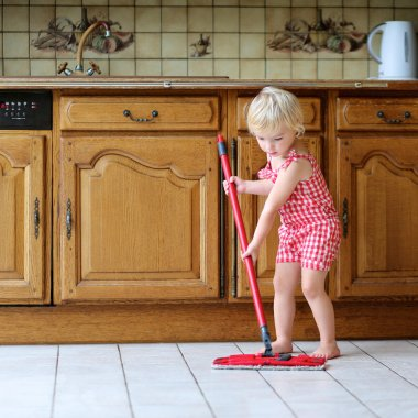 Lovely preschooler girl mopping the floor in kitchen