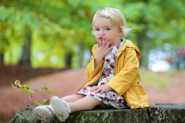 Portrait of cute blonde little child, a toddler girl wearing yellow jacket, sitting on wooden bench in the park stock vector