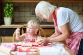 Fotografie Grandmother making cookies with her granddaughter