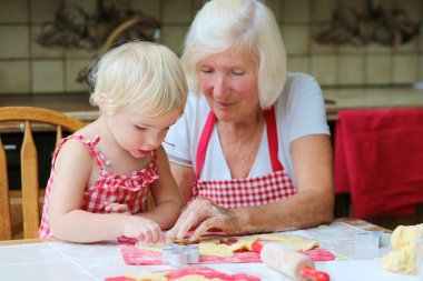 Grandmother making cookies with her granddaughter