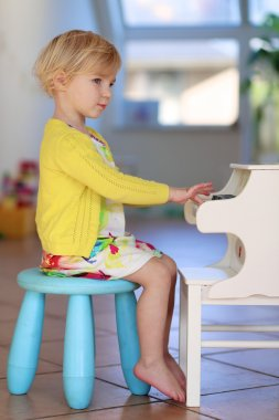 Little girl playing piano toy at home