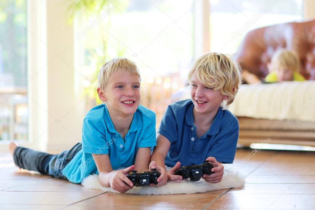two brothers playing video games at home � stock photo
