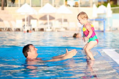 Father and daughter having fun in swimming pool
