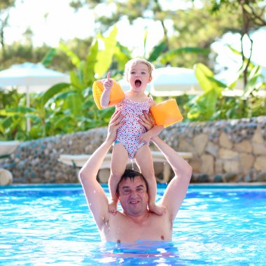 Father with little daughter in swimming pool