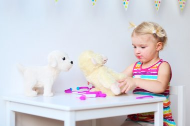 Little girl playing doctor with toys