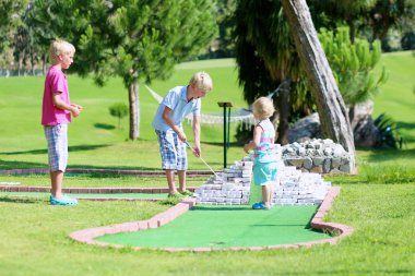 Group of kids playing mini golf outdoors