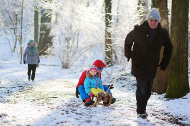 Happy grandfather playing with grandkids in winter