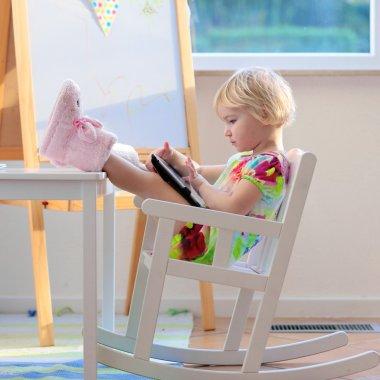 Preschooler girl using tablet pc at home or school