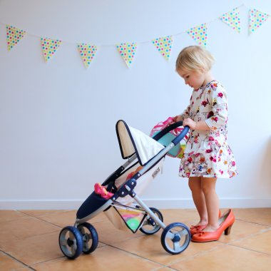 Cute little girl playing with toy pram and doll