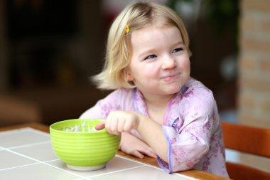 Blonde little girl eating muesli with yoghurt for breakfast