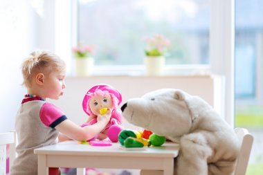 Preschooler girl playing with plastic toys vegetables