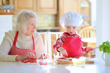 Grandma with granddaughter preparing pizza