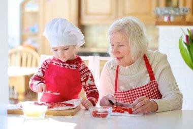 Grandma with granddaughter preparing pizza