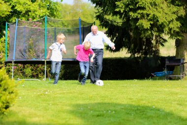 Grandfather with grandsons playing soccer in the garden