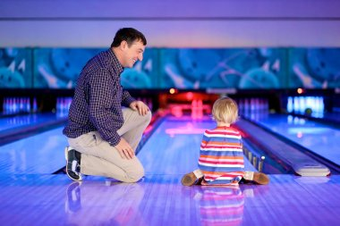 Father and daughter playing bowling
