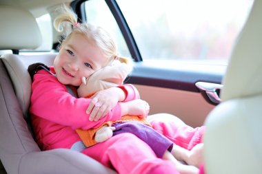 Happy toddler girl enjoying trip in the car