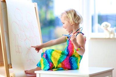Preschooler girl drawing on paper roll