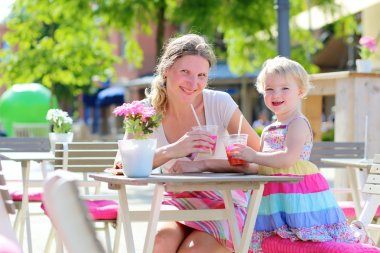 Mother and daughter relaxing in outdoors cafe