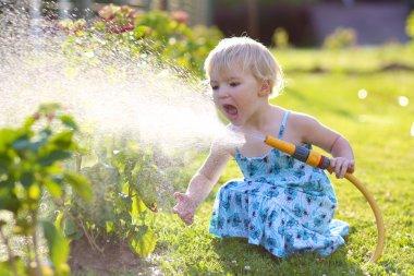 Cute little girl watering flowers in the garden