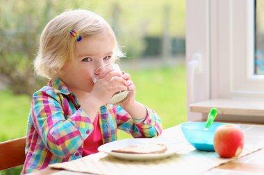 Little girl having toast and milk for breakfast