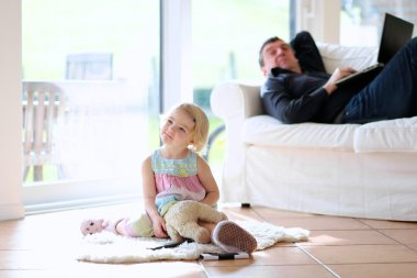 Cute little child, 3 years old preschooler girl watching tv sitting on the tiles floor, her father lying comfortable with laptop on sofa - happy family at home stock vector