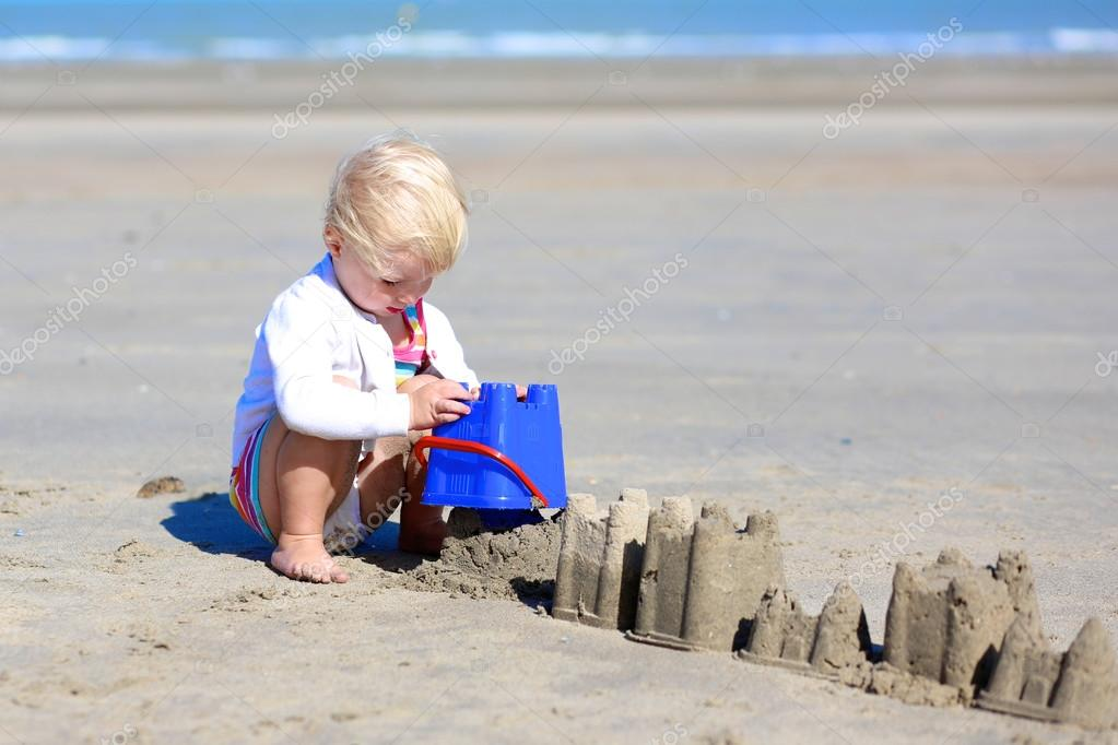 Cute girl building sand castles on the beach