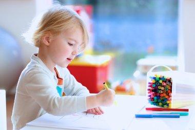 Lovely little girl drawing with felt-tip pens