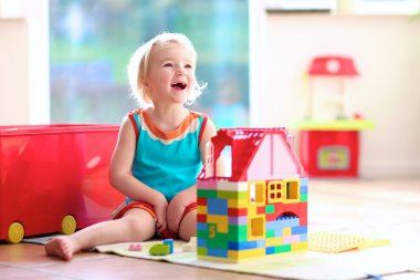 Little girl playing with construction blocks