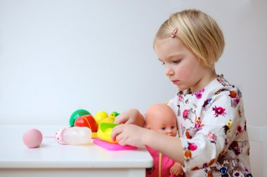 Toddler girl playing with dolls indoors