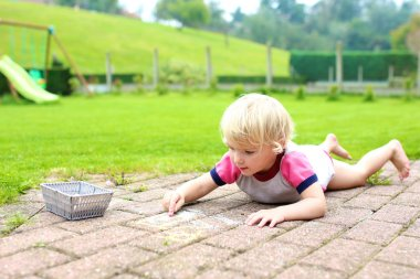 Preschooler girl drawing with chalk outdoors