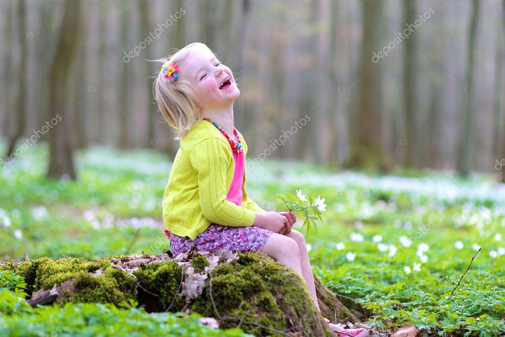 Adorable little girl enjoying spring blooming forest
