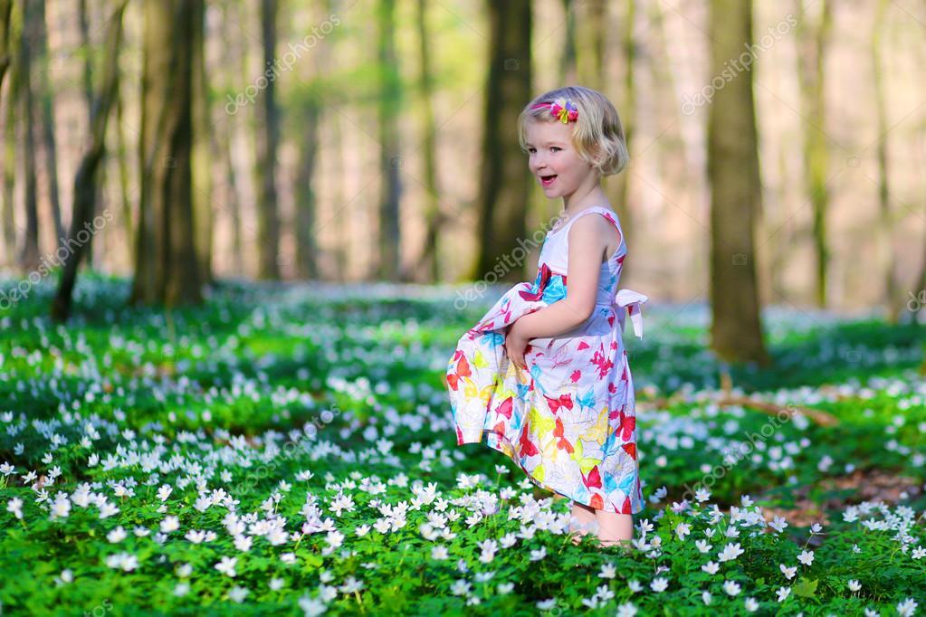 Adorable little girl enjoying spring blooming forest