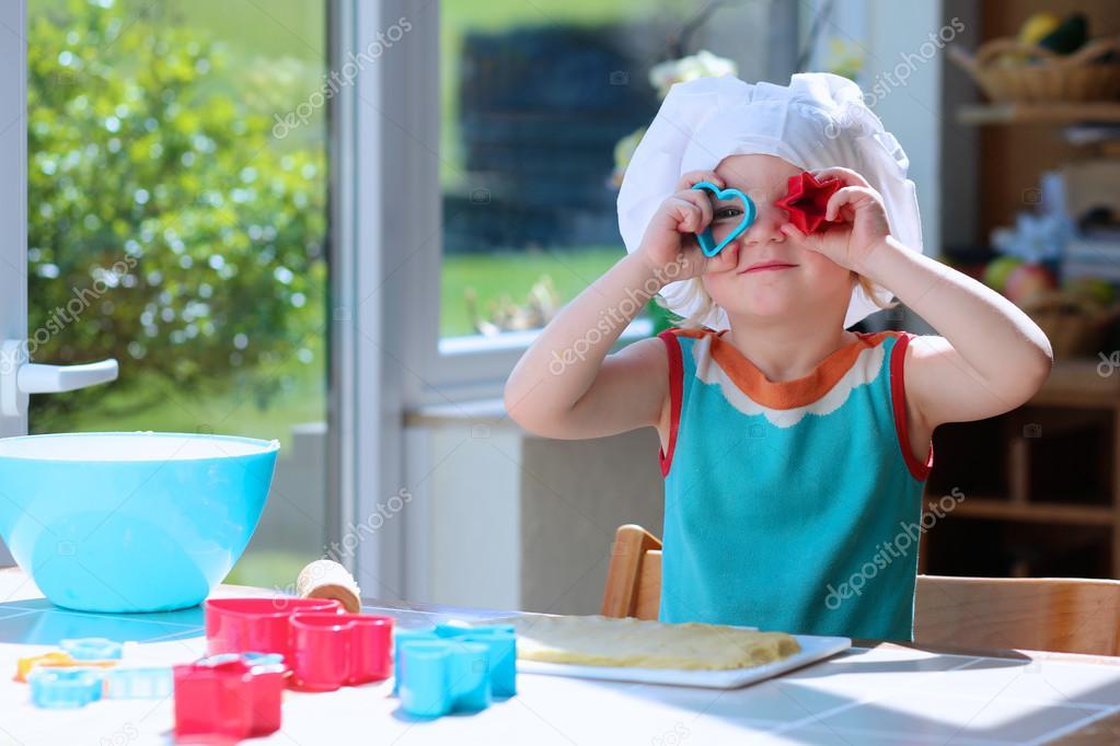 Happy toddler girl preparing cookies