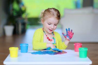 Preschooler girl drawing with finger paint