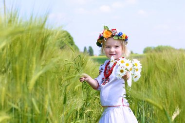 Little girl in Ukrainian dress playing in the field