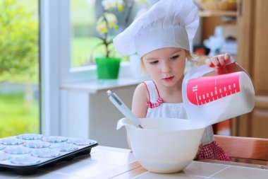 Cute little girl baking pastry in the kitchen